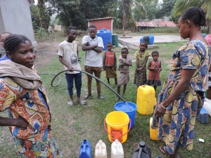 woman and kids around water bucket